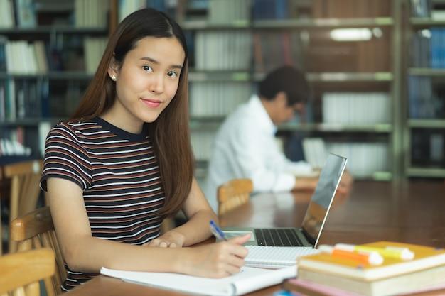 Studente asiatico femminile che studia e che legge libro in biblioteca Foto Premium