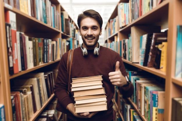 Studente bianco in maglione con libri in navata laterale della biblioteca. Foto Premium