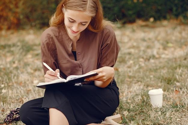 Studente carino che lavora in un parco e utilizza il notebook Foto Gratuite
