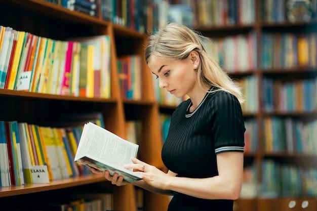 Studente che legge un libro in biblioteca Foto Premium