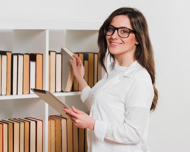 Studente con tavoletta digitale in una biblioteca Foto Gratuite