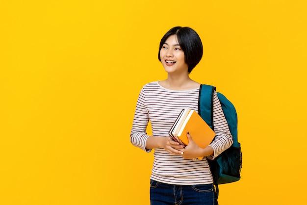Studente di college femminile asiatico con i libri della holding dello zaino Foto Premium