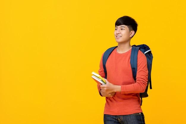 Studente di college maschio asiatico con i libri della holding dello zaino Foto Premium