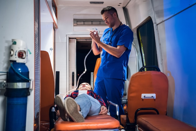 Studente di medicina che ha un esame, preparandosi a dare una maschera di ossigeno al suo paziente in un'auto ambulanza Foto Premium