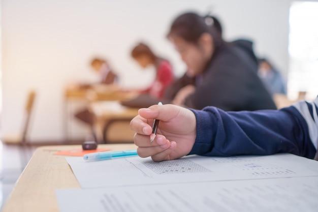 Studente di prova esami in liceo, studente universitario in possesso di matita per testare foglio di risposta esame Foto Premium