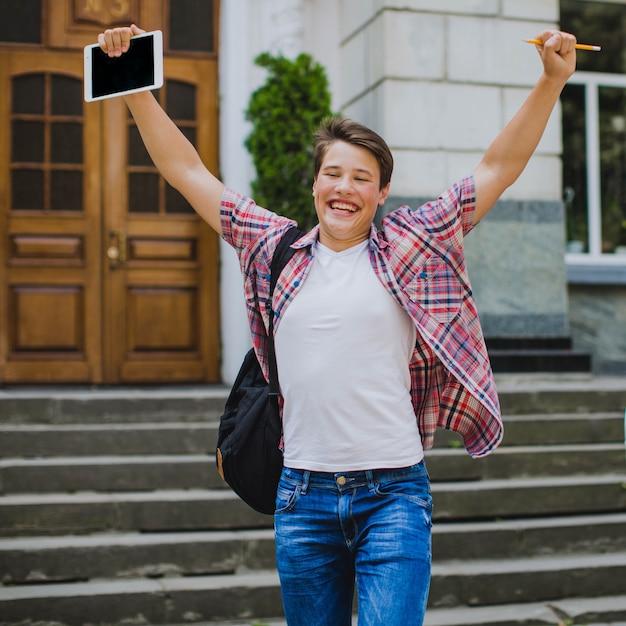 Studente felice in posa con le mani in su Foto Gratuite