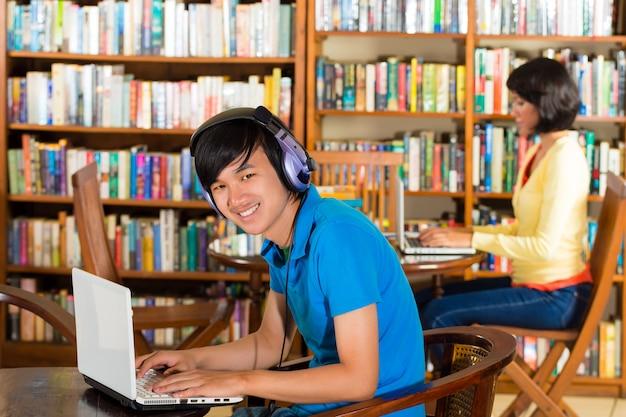 Studente in biblioteca con il computer portatile Foto Premium