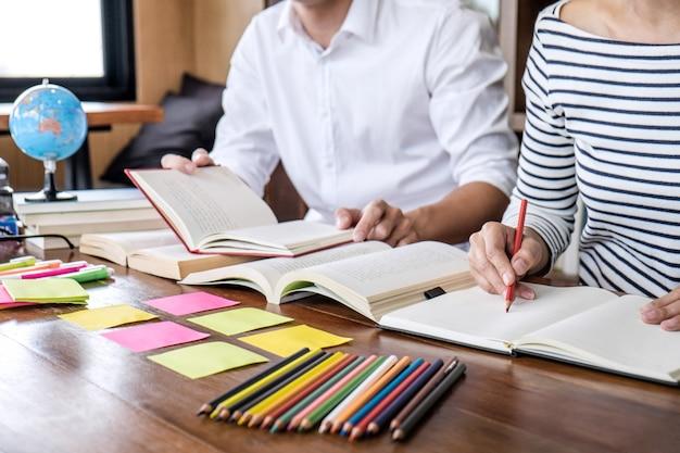 Studente seduto in biblioteca, studiando e leggendo, facendo i compiti e le lezioni di pratica preparazione esame Foto Premium