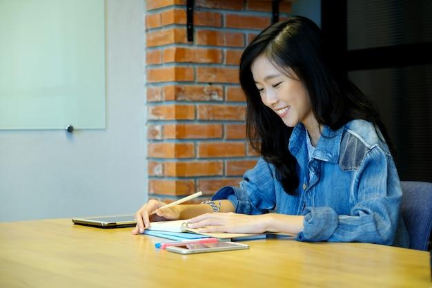 Studente universitario asiatico della donna nella scrittura casuale sul taccuino di carta, Foto Premium