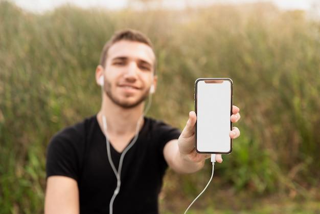 Studente universitario che mostra il suo telefono Foto Gratuite