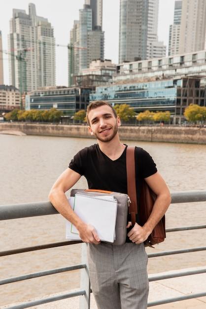 Studente universitario in una grande città con i suoi appunti Foto Gratuite