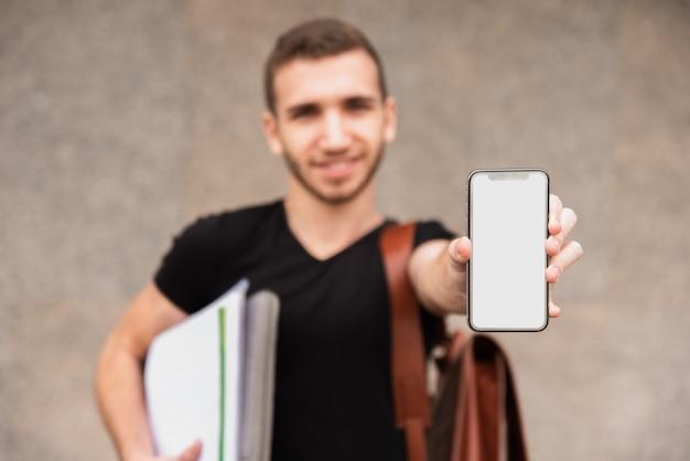 Studente universitario offuscata che mostra il suo telefono Foto Gratuite