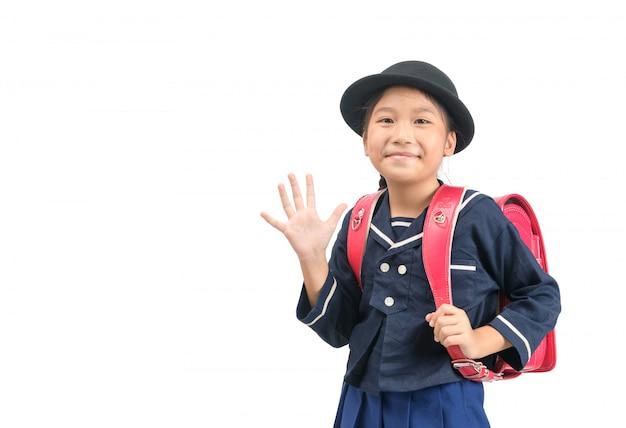 Studentessa asiatica che va a scuola e che ondeggia arrivederci Foto Premium