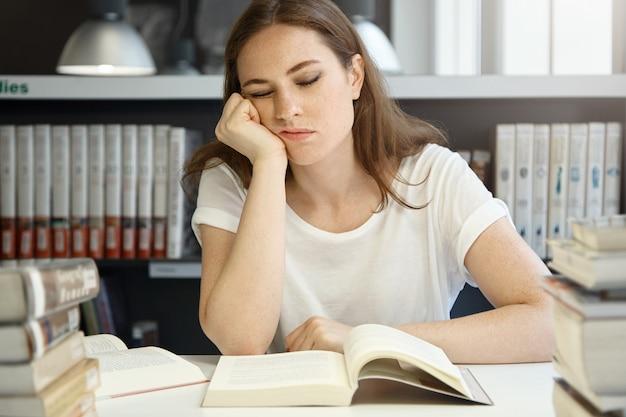 Studentessa caucasica di medicina dell'università che studia alla biblioteca, bella donna del college che dorme mentre seduto di fronte a un libro aperto appoggiato il mento su una mano, guardando esausto. Foto Gratuite