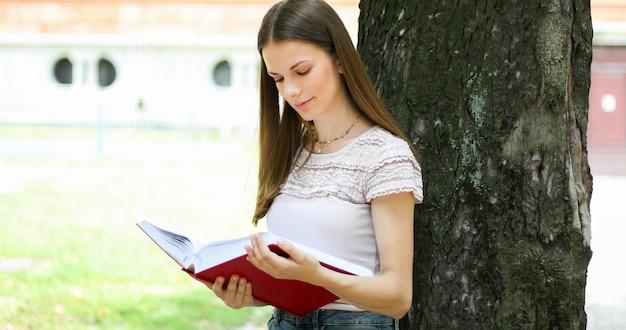 Studentessa che legge un libro all'aperto nel parco che si trova contro un albero e sorridere Foto Premium