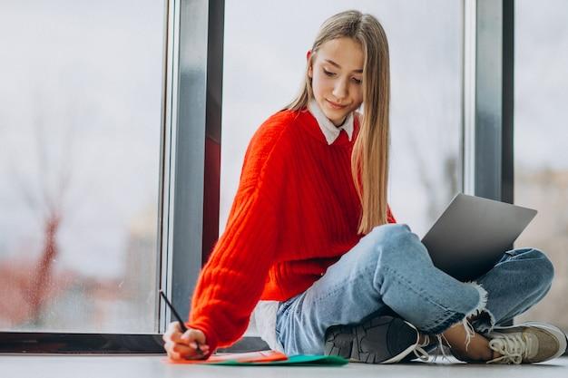 Studentessa che studia sul computer dalla finestra Foto Gratuite