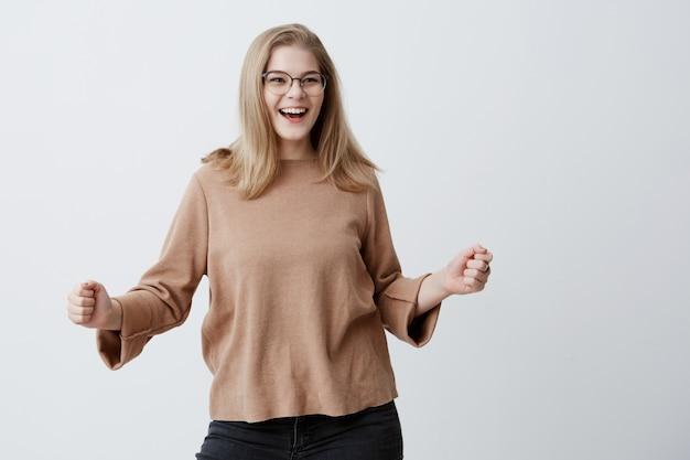 Studentessa fortunata eccitata allegra con capelli biondi e occhiali da vista, tifo, festeggia il successo, urla sì con i pugni chiusi. successo, vittoria, eccitazione e concetto di successo. Foto Gratuite