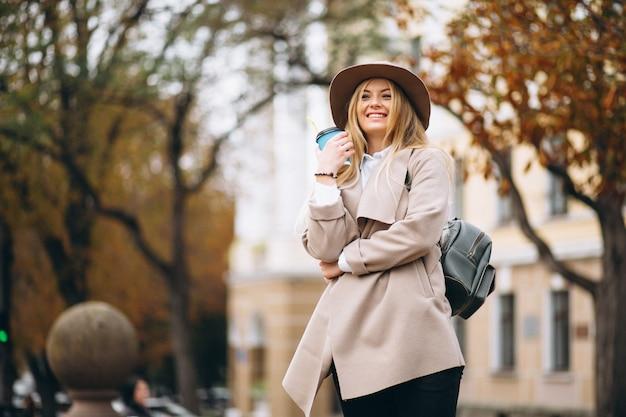 Studentessa in cappello che beve caffè Foto Gratuite