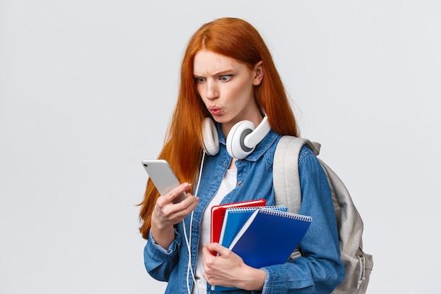 Studentessa rossa di bell'aspetto dispiaciuta, pazza o confusa, studente con zaino, quaderni e cuffie, lettura di strani messaggi sullo smartphone, accigliato, Foto Premium