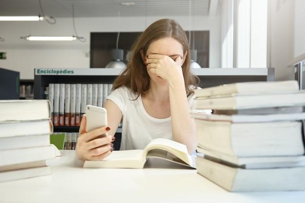 Studentessa stanca della scuola di economia seduta in biblioteca stropicciandosi gli occhi, annoiata di leggere il manuale di audit, controllando il tempo usando la sua applicazione per smartphone, circondata da pile di libri Foto Gratuite