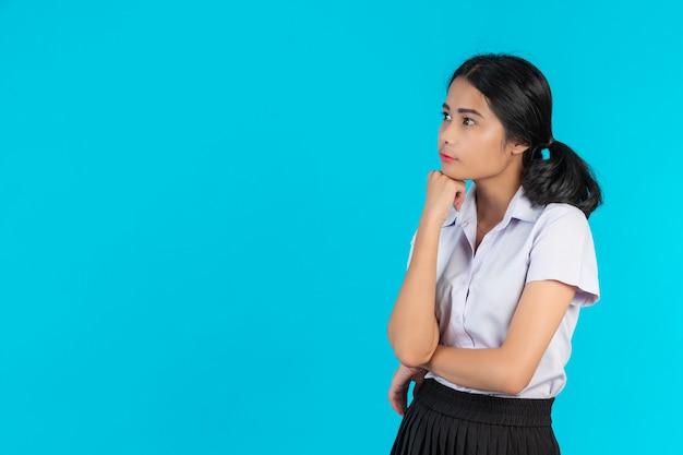 Studentesse asiatiche che eseguono i vari gesti su un blu. Foto Gratuite