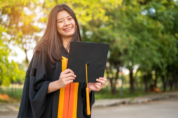 Studentesse con i capelli lunghi che indossano vestiti neri dell'increspatura che esprimono gioia sulla graduazione all'università. Foto Premium