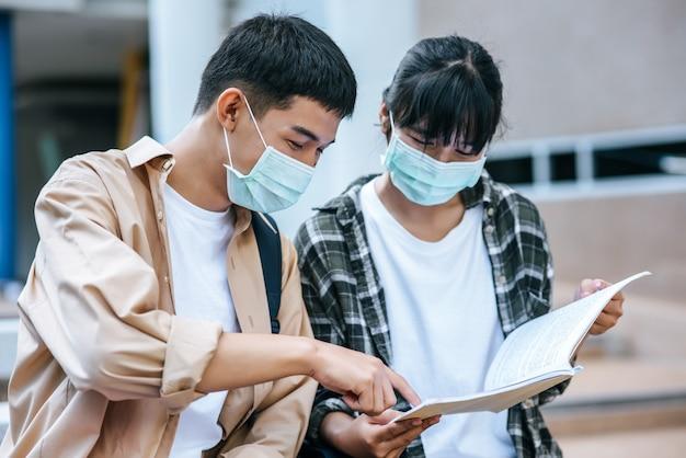 Studentesse e uomini che indossano maschere siedono e leggono libri sulle scale Foto Gratuite