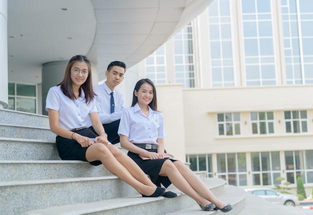 Studenti asiatici felici nell'ubicazione uniforme all'università Foto Premium