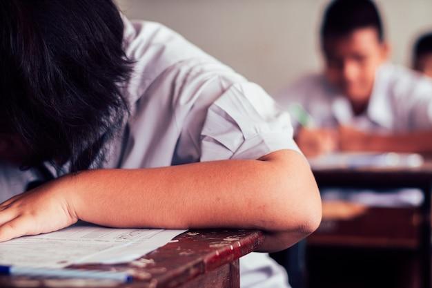 Studenti che scrivono risposta facendo esame in aula Foto Premium