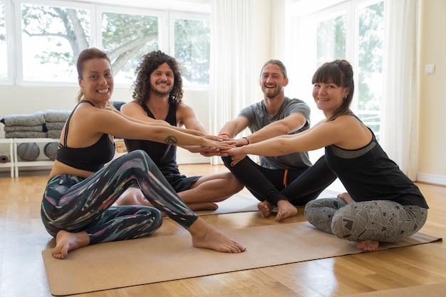 Studenti felici che si tengono per mano insieme dopo la lezione di yoga Foto Gratuite