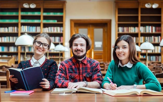 Studenti felici in biblioteca sorridendo alla telecamera Foto Premium