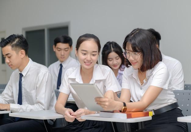 Studenti in uniforme che lavorano con il tablet Foto Premium