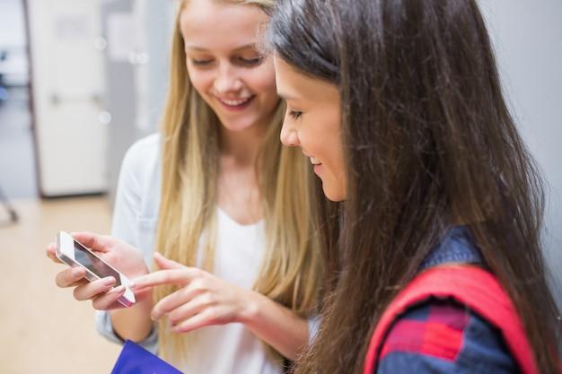 Studenti sorridenti che utilizzano smartphone all'università Foto Premium