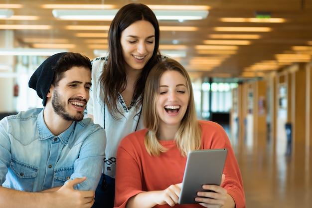 Studenti universitari che utilizzano la compressa digitale nella biblioteca universitaria. Foto Premium