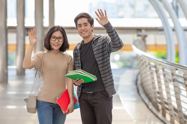 Studenti uomo e donna che tengono molti libri agitando le mani salutano i loro amici Foto Premium