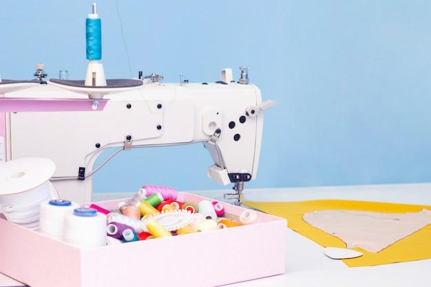 Studio di cucito. macchina da cucire. una serie di articoli per il ricamo: fili, aghi, spille, forbici, metro a nastro, ecc. Foto Premium