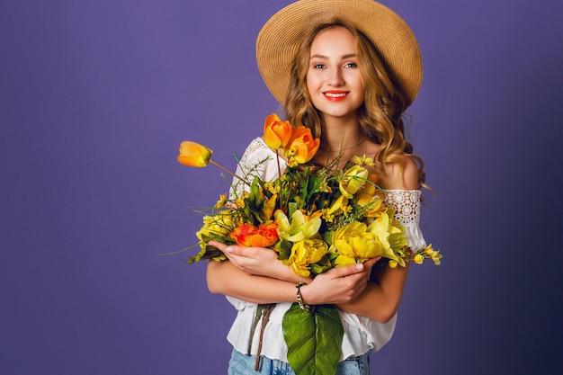 Studio moda ritratto di donna bionda piuttosto carina in cappello di paglia, camicia di cotone bianco seduto e in possesso di bouquet di fiori primaverili incredibili. indossa un elegante abito retrò. Foto Gratuite