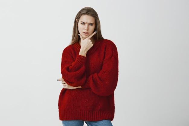 Studio ritratto di donna attraente dubbiosa travagliata in elegante maglione sciolto rosso, tenendo il gesto della pistola sul mento e accigliato, sentendosi sospettosa e frustrata, in piedi Foto Gratuite