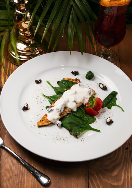 Stufato di pesce in salsa cremosa, pomodoro, prezzemolo sul piatto, coltello, forchetta Foto Gratuite