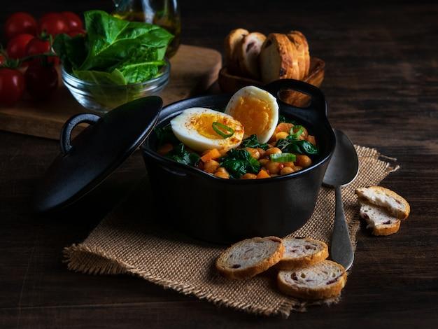 Stufato spagnolo di spinaci e ceci con uova su fondo di legno rustico. cucina spagnola Foto Premium