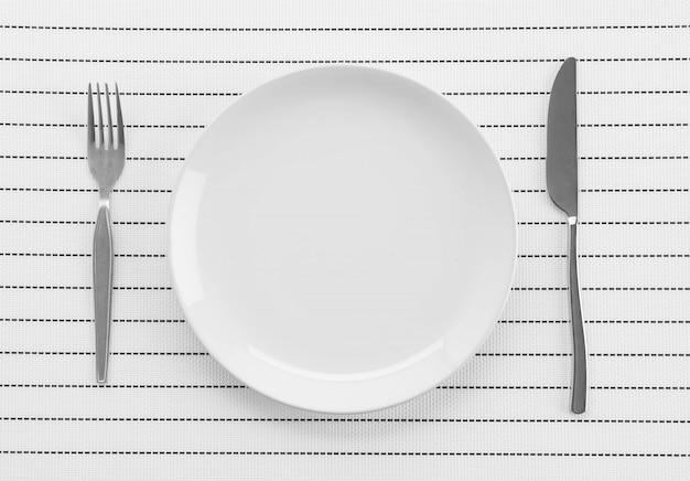 Stuoia a piastra con forchetta e coltello a piastra Foto Gratuite