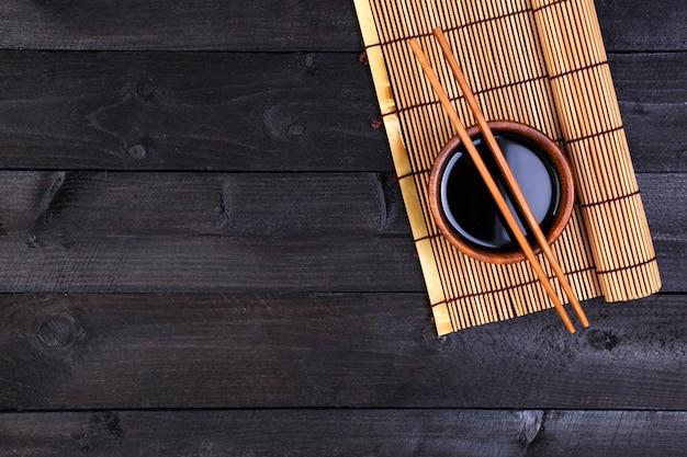 Stuoia di bambù e salsa di soia sul tavolo di legno scuro. Foto Premium