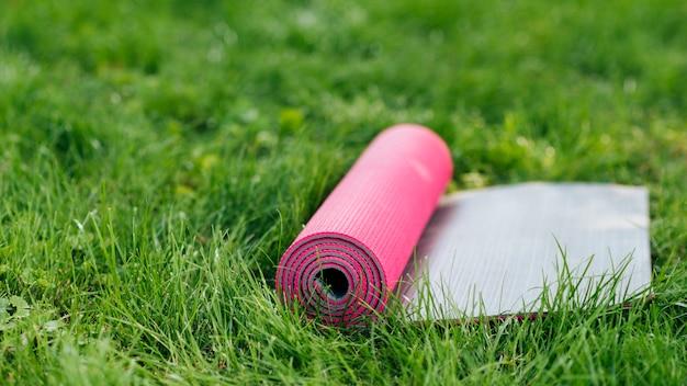 Stuoia rosa di yoga su erba Foto Gratuite