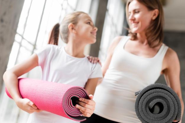 Stuoie felici di yoga della tenuta della figlia e della madre Foto Gratuite