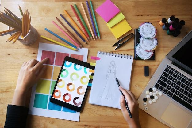 Stylish fashion designer lavora come schizzo di una nuova collezione in atelier. concetto di design creativo Foto Premium