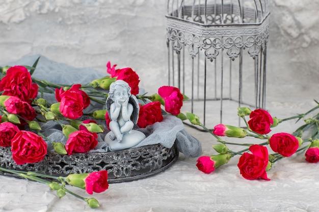 Su uno sfondo grigio garofani luminosi su un vassoio grigio, una gabbia e una figura di un angelo Foto Premium