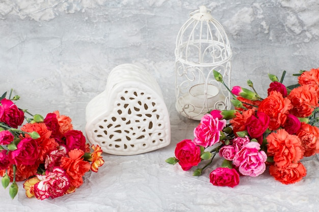 Su uno sfondo grigio, garofani luminosi, un cuore di trafori fatto di ceramica e una gabbia decorativa bianca Foto Premium