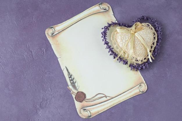 Su uno sfondo lilla un foglio di carta e un cuore di pizzo: un invito, un saluto Foto Premium