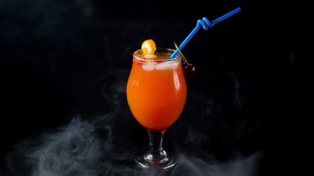 Succo d'arancia con ciliegie rosse pipa blu e cubetti di ghiaccio. Foto Gratuite