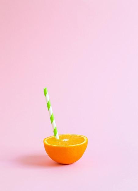 Succo d'arancia con tubulo. arancia tagliata a metà su sfondo rosa pastello. Foto Premium